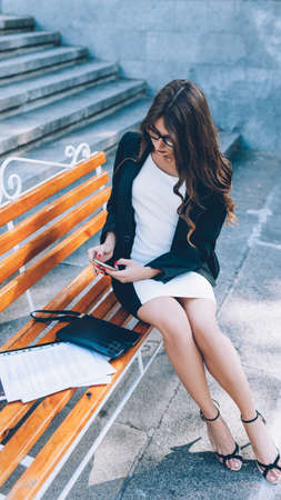 Female lifestyle. Successful career. Confident business woman sitting on bench with phone papers.