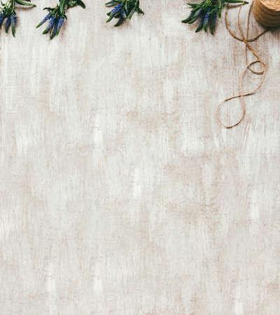 Florist workplace. Natural decorative arrangement. Wildflowers cord on beige textured background.