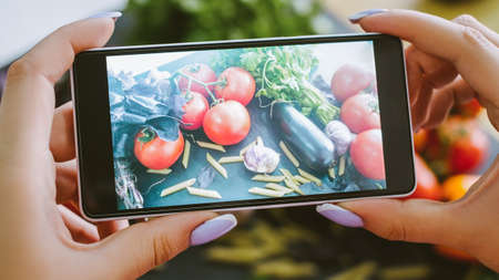 Food blog. Healthy nutrition. Woman taking picture of fresh vegetables pasta on smartphone camera.