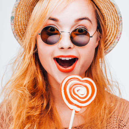 Summer joy. Happiness fun surprise. Amazed hipster girl with lollipop. Zdjęcie Seryjne