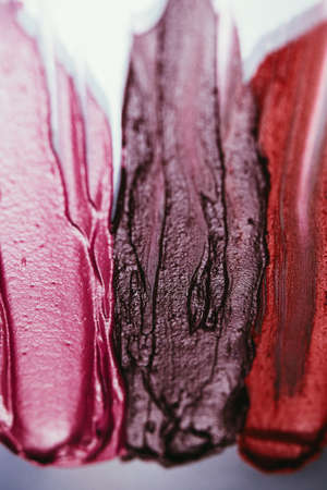 Lipstick palette. Decorative cosmetic products. Dark textured strokes. Art background.