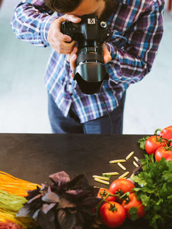 Food photography. Creative presentation promotion. Male stylist taking picture of fresh vegetables.