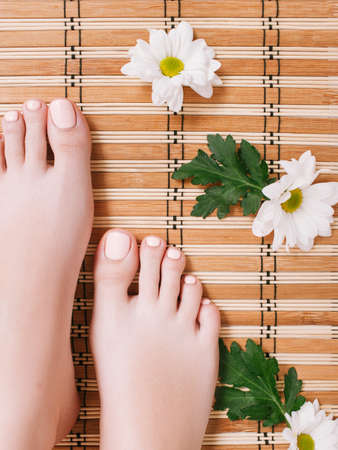 Spa therapy. Skin care procedure. Pedicure. Female feet on beige bamboo roll up mat. Zdjęcie Seryjne