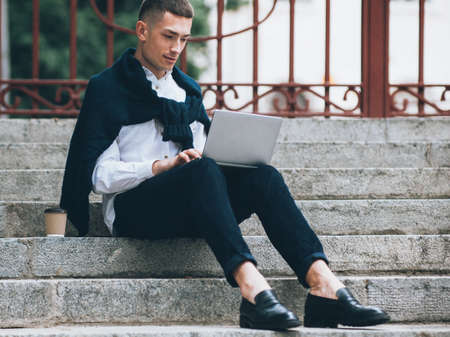Online business. Modern technology. Stylish man sitting on stairs working on laptop.
