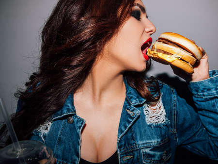 Fast food addiction. Delicious american meal. Woman enjoying eating burger. Zdjęcie Seryjne