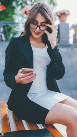 Social media. Online communication. Cheerful business woman using mobile phone.
