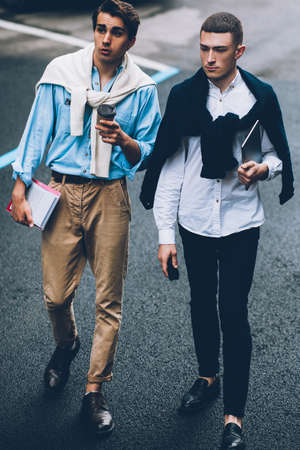 Modern lifestyle. Social communication friendship. Two swanky guys walking on urban street.