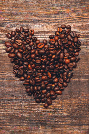 Romantic background. Valentine day. Coffee beans heart on brown wooden surface.