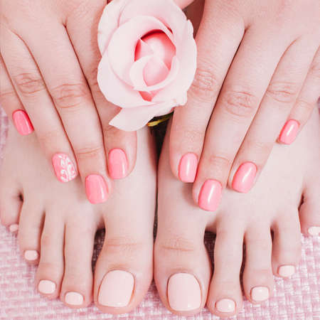 Nail studio. Foot care. Manicure pedicure. Female hands feet. Peach color polish. Zdjęcie Seryjne - 131259524