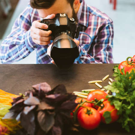 Food photography. Vegetarian lifestyle blog. Male stylist taking picture of organic ingredients.