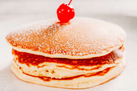 Traditional American food. Homemade pancakes. Crepe stack with sugar powder cherry on top. Zdjęcie Seryjne