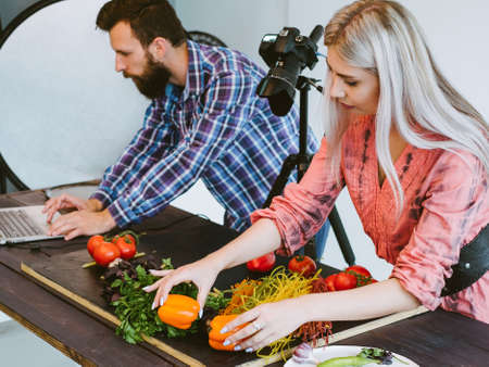 Object photo shoot. Teamwork creativity. Female assistant helping designer to arrange vegetables. Standard-Bild - 132330679