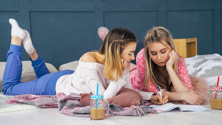 Women leisure. Relaxed lifestyle fun. Girls hanging out on floor at home drawing chatting. Stock Photo