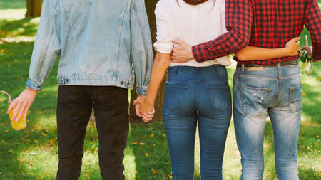 Polyamorous relationship. Love affection partnership. Woman standing with two guys in nature park.