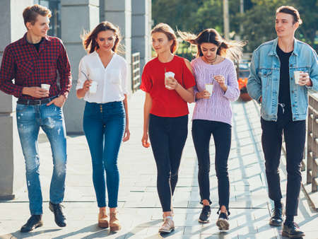 Teens leisure. Social communication fun. Group of male female friends walking with take away coffee.