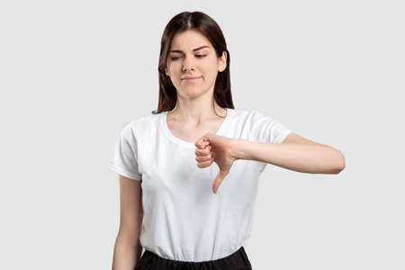 Dislike gesture. Not cool. Criticizing woman showing thumb down isolated on neutral background.