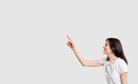Commercial background. Special offer. Amused woman isolated pointing up at light empty space.