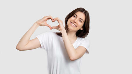 Love sign. Compassion support. Happy woman showing heart gesture isolated on neutral background.