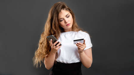 Mobile banking. E-commerce payment. Confident woman using credit card smartphone isolated on gray.