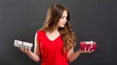 Birthday present. Holiday shopping. Woman in red choosing between 2 gift boxes isolated on gray background.