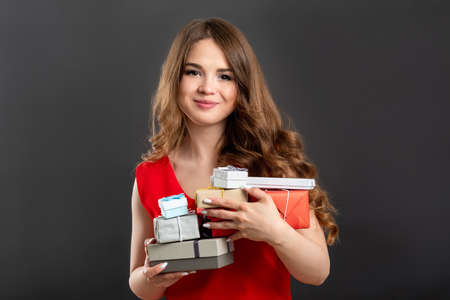 Holiday shopping. Big sale. Happy woman in red holding gift boxes isolated on gray background.