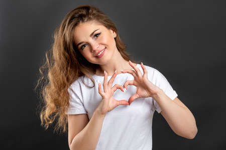 Love sign. Romantic message. Cheerful woman showing heart gesture isolated on gray background. Standard-Bild