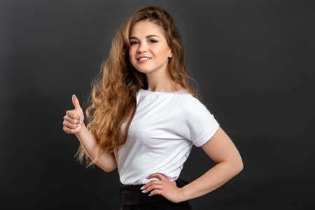 Like gesture. Encouragement admiration. Confident woman showing thumb up isolated on gray background.