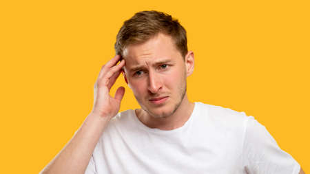 Troubled man portrait. Frustration anxiety. Worried guy touching head thinking isolated on orange background. Standard-Bild