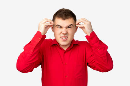 Frustrated man portrait. Nervous breakdown. Angry guy in red shirt touching head isolated on white background.