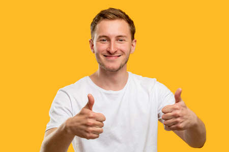 Like gesture. Perfect choice. Satisfied man smiling showing thumbs up isolated on orange background.
