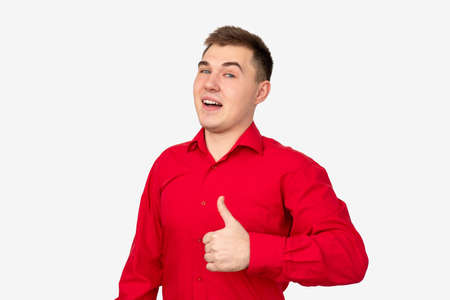 Like gesture. Perfect choice. Confident man in red shirt supporting with thumb up isolated on white.