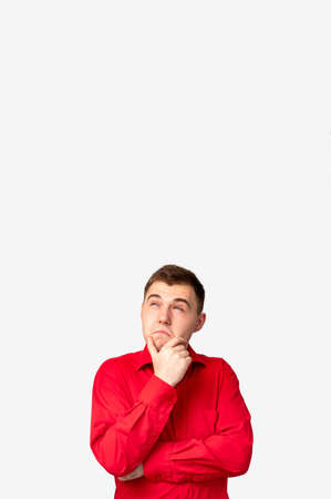 Ad background. Special offer. Doubtful man in red shirt isolated considering option on white copy space.