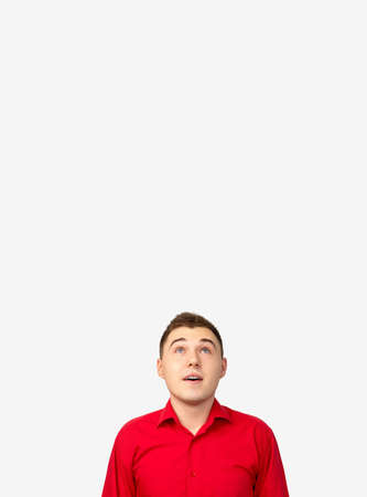Promotional background. Special offer. Amazed man in red shirt isolated on white copy space.