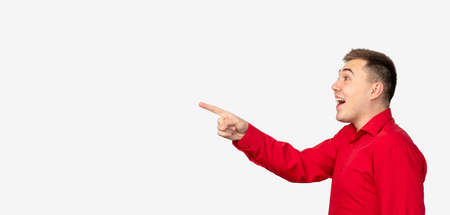 Commercial background. Special offer. Surprised man in red shirt isolated pointing at white copy space.