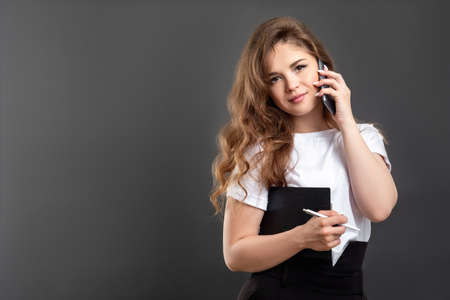 Business call. Professional communication. Confident woman using mobile phone isolated on gray copy space.