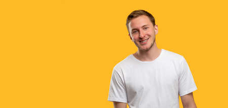 Cheerful man portrait. Success achievement. Friendly guy smiling isolated on orange copy space background. Standard-Bild