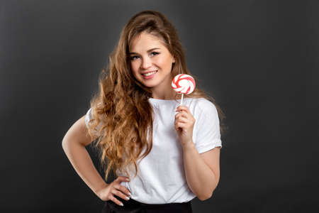 Carefree woman portrait. Fun lifestyle. Playful lady smiling holding lollipop isolated on gray background.