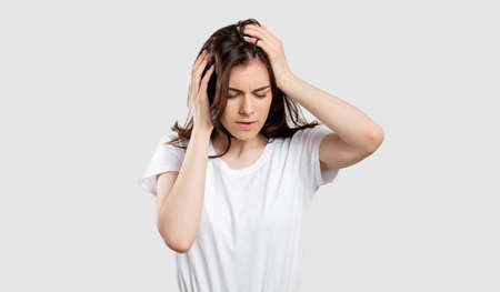 Suffering woman portrait. Migraine pain. Stressed out lady touching head isolated on neutral background. Standard-Bild