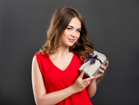 Holiday present. Special offer. Cheerful woman in red showing gift box isolated on gray background.