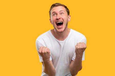 Lucky man portrait. Victory gesture. Amused guy celebrating triumph shouting isolated on yellow background.