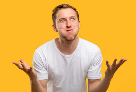Amazed man portrait. Special offer. Excited guy raising hands isolated on yellow background. Standard-Bild