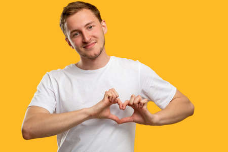 Love sign. Compassion support. Friendly man in white t-shirt showing heart gesture isolated on orange.