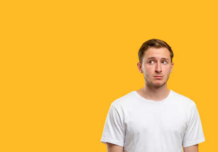 Confused man portrait. Announcement background. Doubtful guy isolated looking curiously at orange copy space. Standard-Bild