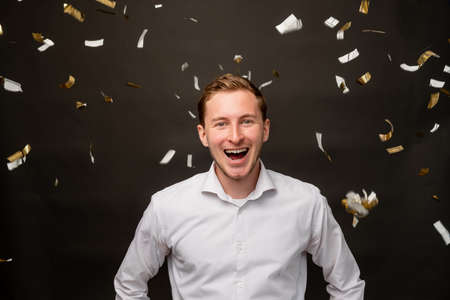 Festive portrait. Fun celebration. Amused man smiling in confetti rain isolated on black background.