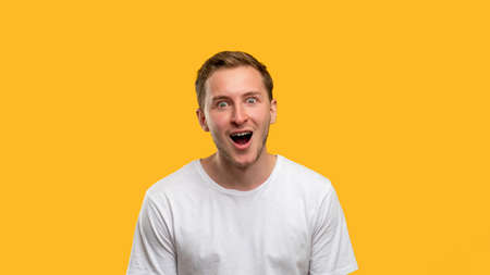 Amazed man portrait. Great news. Surprised guy with open mouth isolated on yellow empty space background. Standard-Bild