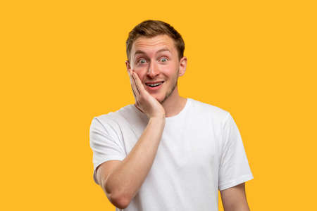 Omg portrait. Success enthusiasm. Confused man with hand on cheek smiling isolated on yellow background. Banque d'images