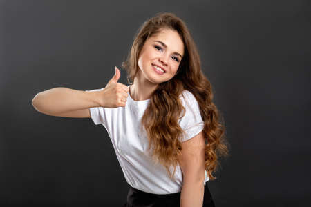 Like gesture. Good idea. Cheerful woman showing thumb up isolated on gray background.