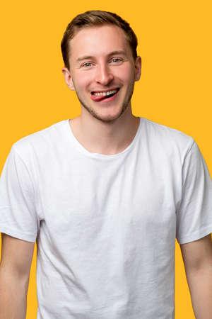 Funny man portrait. Carefree lifestyle. Enthusiastic guy sticking tongue out smiling isolated on orange.