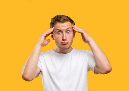 Frustrated man portrait. Panic attack. Stressed out guy touching head isolated on orange background. Standard-Bild
