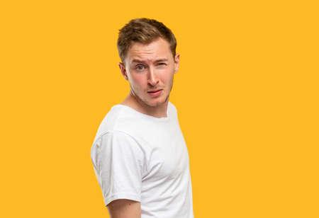 Suspicious man portrait. Warning look. Skeptic guy raising eyebrow isolated on orange background. Standard-Bild